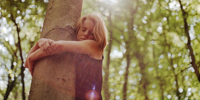 Young woman hugging tree, eyes closed